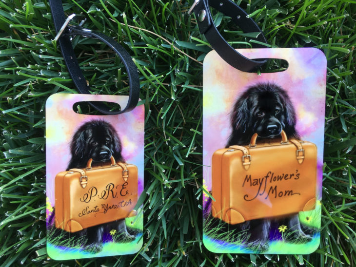 Image of luggage tags, in which a dog holds a suitcase emblazoned with a custom name upon it